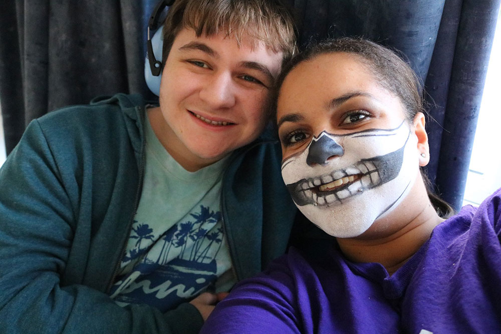 Play Worker with face painted smiling with young person