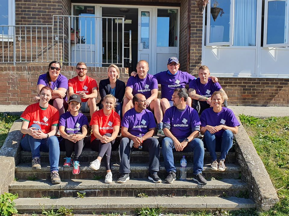 12 people sat in two rows on a set of stairs wearing Extratime t-shirts at Portslade Village Centre