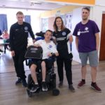 One wheelchair user and three people standing in a hall at Portslade Village Centre