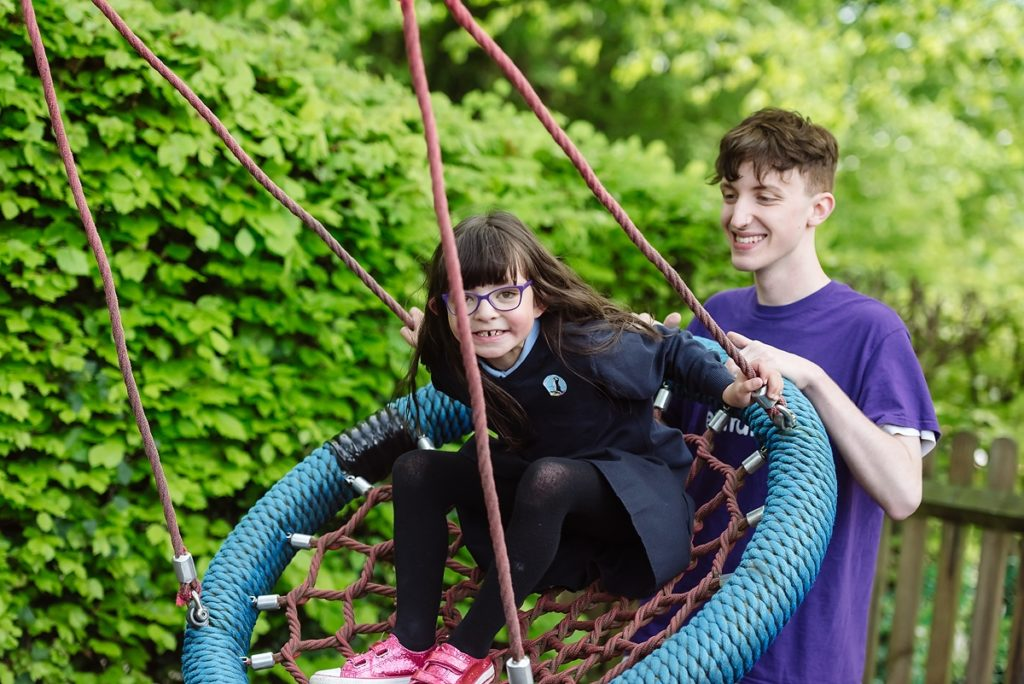 Play Worker pushing young person on swing